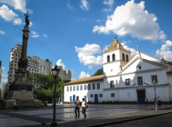 """EL ORIGEN DE SÃO PAULO Pocas ciudades tienen una fecha de nacimiento tan específica como la selva de piedra. El 25 de enero de 1554, en lo alto de una colina entre los ríos Tamanduateí y Anhangabaú, un grupo de jesuitas, entre los que se encontraban los padres Manuel de Nóbrega y José de Anchieta, celebraron una misa en una pequeña cabaña improvisada para la ocasión. Así nacía São Paulo de Piratininga, bautizada de esa forma por ser el día en el que la iglesia católica conmemora la conversión de San Pablo, y porque """"Piratininga"""", que en tupí guaraní significa """"pez seco"""", era el nombre con el que las comunidades locales conocían esa región. Alrededor de esa cabaña, que se encontraba en el lugar de la fotografía, fue construido un colegio y poco a poco fueron asentándose los nativos americanos que se convertían a la religión cristiana. Con el paso de los años, aquella pequeña aldea daría lugar a la mayor ciudad de América del Sur. Actualmente, en ese lugar conocido como """"Pátio do Colégio"""" se encuentran una iglesia y un museo. La construcción del recinto no es original, sino una réplica de la que había cuando los jesuitas fueron expulsados de Brasil en 1759 por sus constantes enfrentamientos con las autoridades de la colonia. En 1954, con motivo del 400 aniversario de la ciudad, el terreno fue devuelto a la Compañía de Jesús y finalmente, en 1979, fue inaugurado el actual """"Pátio do Colégio""""."""
