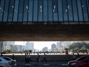 """EL MASP Y SU """"HUECO"""" El Museo de Arte de São Paulo Assis Chateaubriand, más conocido como MASP, está situado en plena Avenida Paulista, corazón de la ciudad de São Paulo. Sus salas albergan, además de obras de artistas brasileños consagrados como Portinari, Anita Malfatti o Cavalcanti, la más importante muestra de arte europeo de todo el hemisferio sur. Van Gogh, Degas, Renoir, Picasso, Modigliani, Chagall… son algunos de los integrantes de su acervo. Pero, ¿cómo llegaron hasta Brasil las obras de autores europeos tan cotizados mundialmente? La respuesta está en la persona que da nombre al museo: Assis Chateaubriand. Emprendedor incansable, Assis Chateaubriand poseía a mediados del siglo XX el mayor imperio de medios de comunicación de Brasil, formado por periódicos, revistas y estaciones de radio. Una nueva idea se le metió en la cabeza: el país necesitaba un centro difusor de cultura al nivel de los que había en países más desarrollados. Para crear esa institución ofreció, a cambio de donaciones, espacios publicitarios en sus medios a los adinerados empresarios paulistanos, cuyas industrias crecían a toda máquina en aquella época. Con los fondos recaudados, y en compañía de su amigo y asesor artístico, el italiano Pietro Maria Bardi, recorrió Europa en busca de obras que elevaran la categoría del futuro museo. La situación no podía ser más propicia para esa empresa, pues en una Europa devastada que acaba de salir de la Segunda Guerra Mundial y comenzaba a reconstruirse, muchas colecciones se vendían a precio de saldo. Poco a poco fueron conformando el acervo del que llegaría a ser el museo más importante de América Latina. La primera sede del MASP fue inaugurada en 1947 y se encontraba en el centro antiguo de São Paulo. La de la foto es la sede actual desde 1968 y fue diseñada por Lina Bo Bardi, mujer de Pietro Maria Bardi. Su aspecto externo, con cuatro grandes pilares sujetando el cuerpo principal , no es casual. La Avenida Paulista, en la que se encuentra el MA"""