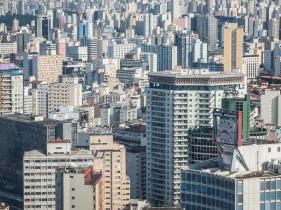 """A SELVA DE PEDRA La """"selva de piedra"""". Así es como su habitantes se refieren a São Paulo, capital económica de Brasil y la mayor ciudad de América del Sur. Contando toda el área metropolitana su población supera los 20 millones de habitantes. Pero no siempre fue así. La villa de São Paulo de Piratininga fue fundada en 1554, y durante sus tres primeros siglos de vida, no pasó de ser una ciudad pequeña y rural. Sería el cultivo del café, en la segunda mitad del siglo XIX, el que dispararía el crecimiento vertiginoso de la ciudad. Inmigrantes venidos de otras partes del país y de todos los rincones del mundo, llegaban en masa a trabajar en las plantaciones de café primero, y en la creciente industria después. Italianos, españoles, japoneses, turcos, alemanes, polacos, libaneses, y armenios entre otros, fueron formando rápidamente la base de la que hoy en día es una de las ciudades más multiculturales de todo el mundo. Aunque la primera impresión para el visitante sea la de una ciudad gris, caótica y hostil, adentrarse en la selva de piedra es una experiencia única, intensa y enriquecedora. En sus calles conviven todos los extremos y todos los matices. Cualquier cosa que exista en el mundo debe tener al menos un ejemplar en São Paulo. O más."""