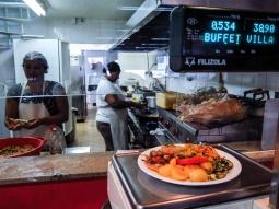 """COMIDA DE KILO Algunos restaurantes brasileños venden la comida por peso. Son los denominados """"kilos"""". Para comer en ellos tienes que coger un plato y servirte lo que te apetezca. Después pasas por la balanza para que te lo pesen y calculen el precio, que varía según el establecimiento. Allí aprovechas también para pedir la bebida, que te la llevarán a la mesa, y ya puedes sentarte a comer."""