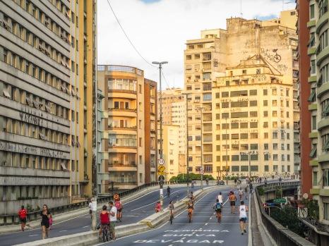 """MINHOCÃO Los problemas con el tráfico son antiguos en la ciudad de São Paulo. A principios de la década de los 70, en un intento por aligerar el intenso tráfico del centro de la ciudad, fue construido el """"Elevado Presidente Costa e Silva"""", una vía expresa de más de 3 km de longitud que discurre unos metros por encima del suelo. Los habitantes de la selva de piedra lo conocen como """"minhocão"""" que en español quiere decir lombriz grande. Desde el primer momento su construcción fue polémica debido al agresivo impacto en los edificios vecinos. Recientemente ha sido aprobado su futuro desmantelamiento y ahora se debate si desmontarlo completamente o transformarlo en un parque, algo que ya ocurre de lunes a sábado entre las 21:30 y las 6:30, y los domingos y festivos durante todo el día, cuando la circulación de coches está prohibida."""